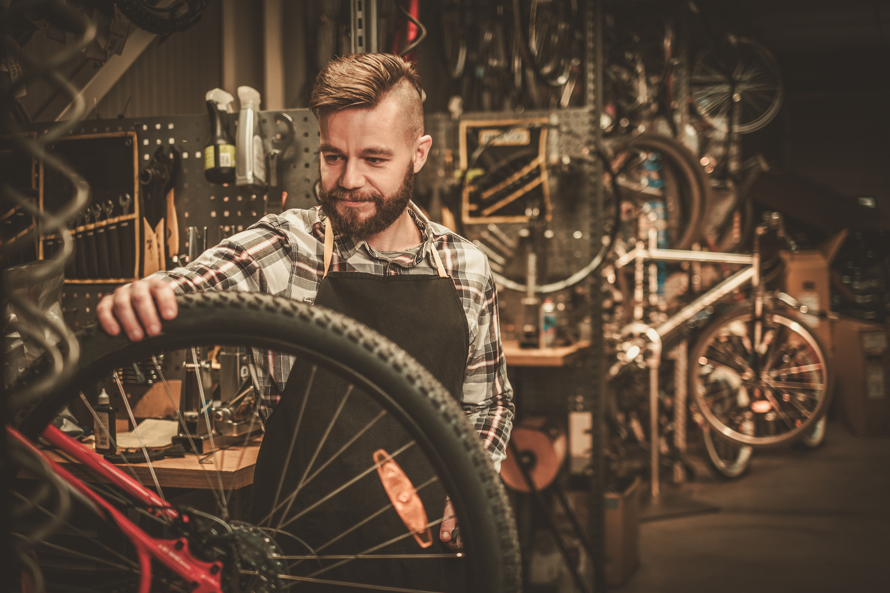 LEED Mechanic measures a bicycle wheel to convert the bike to electric with an e-bike kit.